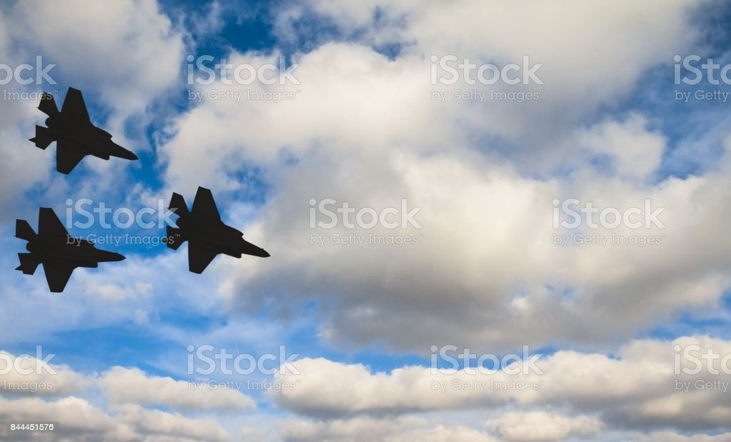 Silhouettes of three F-35 aircraft against the blue sky and white clouds stock photo