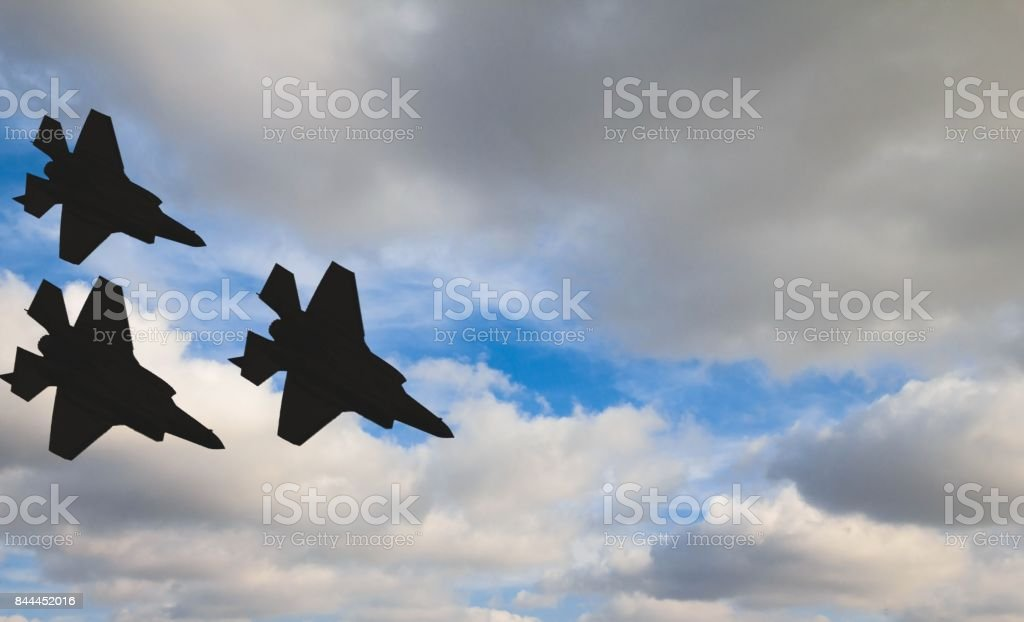Siluetas de tres aviones F-35 contra el cielo azul y nubes blancas - foto de stock