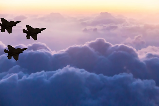 Silhouettes Of Three F35 Aircraft On Sunset Sky Background Stock Photo - Download Image Now