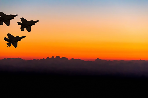 Silhouettes Of Three Super Modern Fighterbomber Aircraft On Sunset Sky Background Stock Photo - Download Image Now