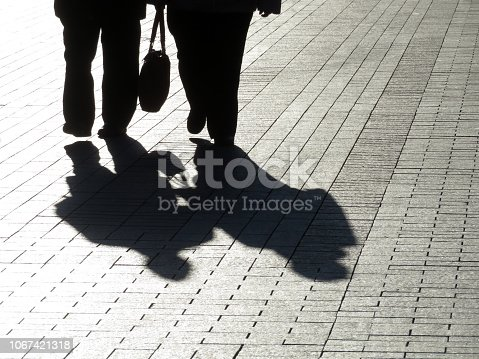 Elderly couple outdoors, shadows on pavement, fat people