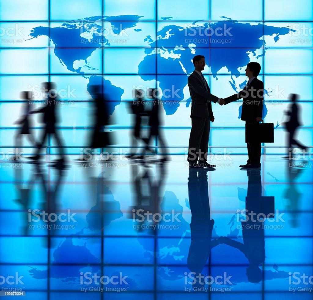Silhouettes of two business men giving a handshake royalty-free stock photo