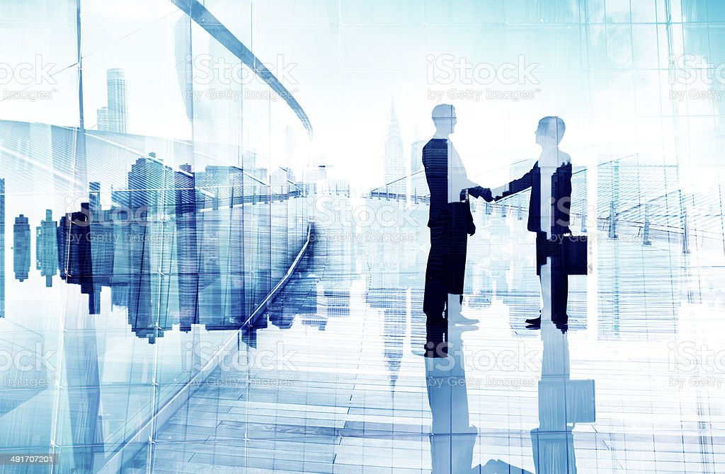Silhouettes of Two Business People Having a Handshake stock photo