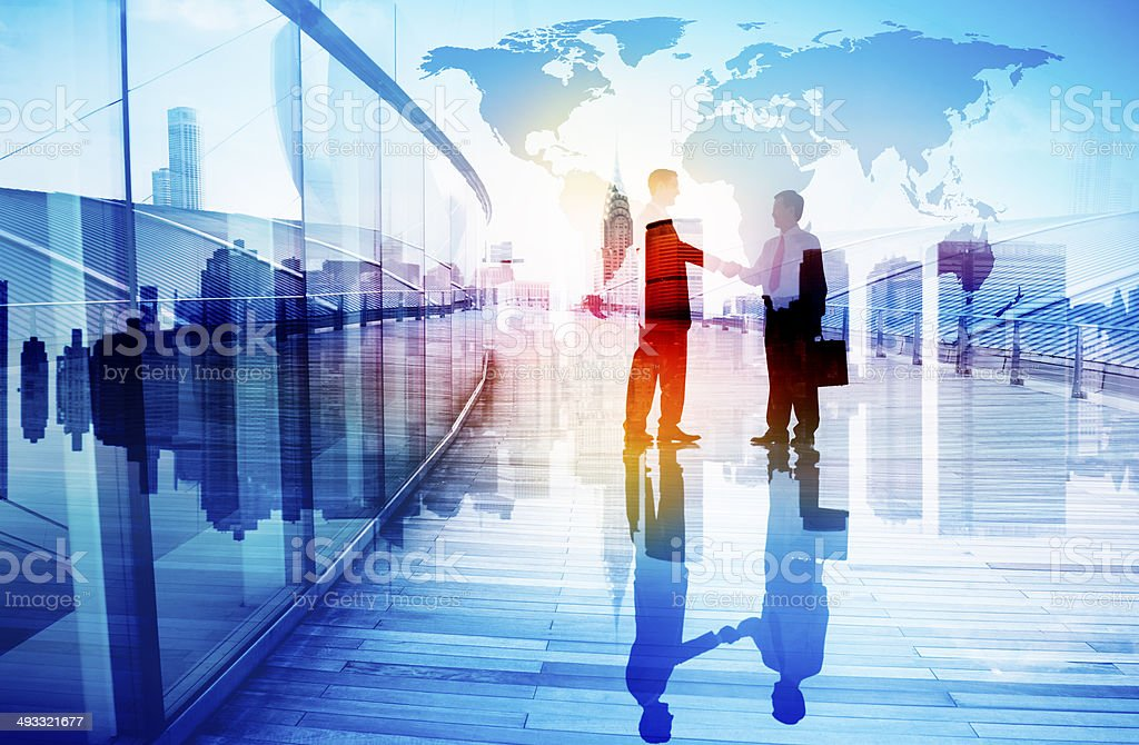 Silhouettes of Two Businessman Shaking Hands stock photo