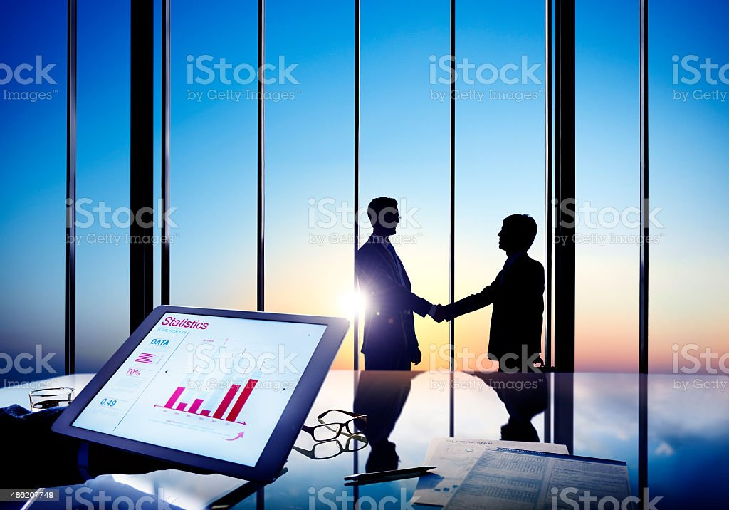 Silhouettes Of Two Businessmen Shaking Hands Together In A Board stock photo
