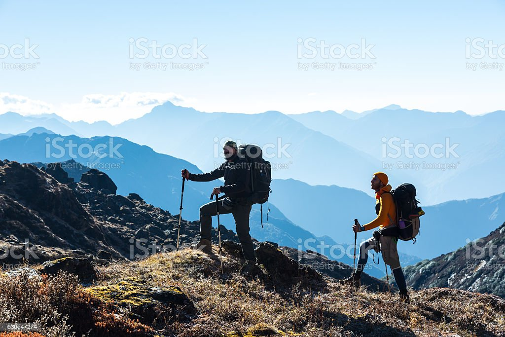Silhouettes of two Hikers in front of Morning Mountains View – Foto