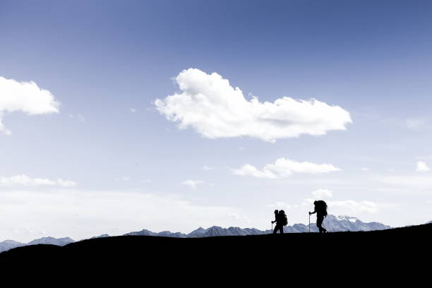 Silhouetten von zwei Wanderern, die am Felsrand entlang laufen – Foto