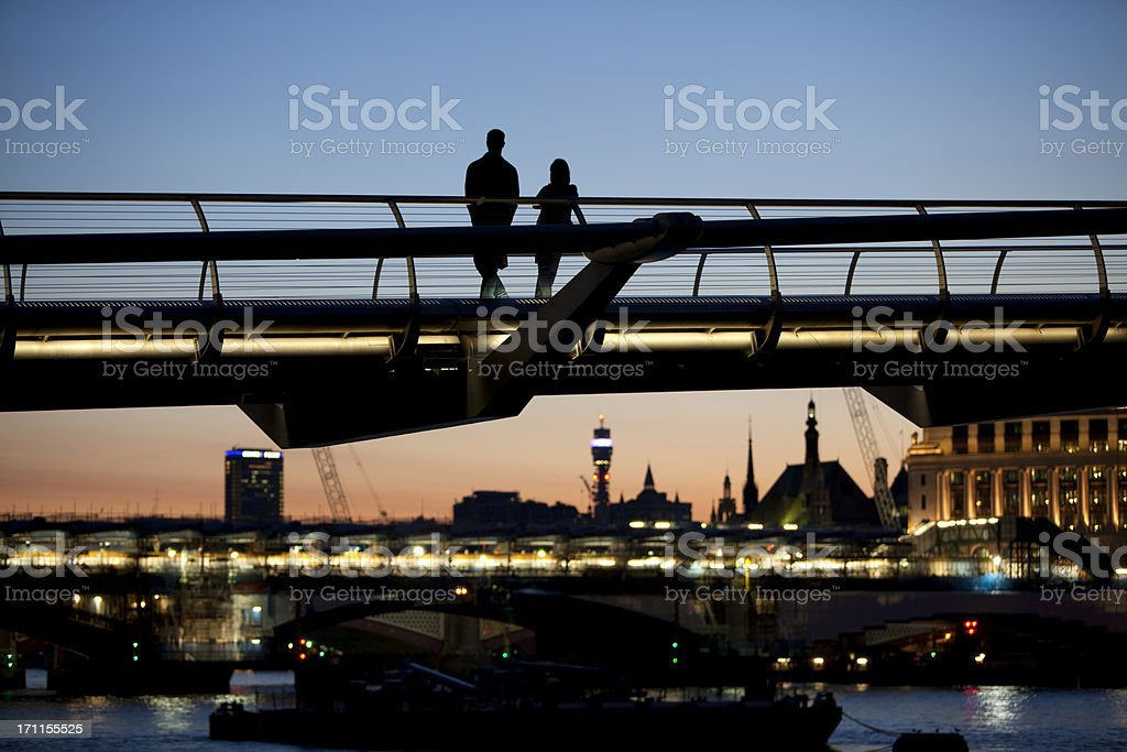 Silhouettes of Two Lovers on Millennium Bridge at Twilight, London royalty-free stock photo