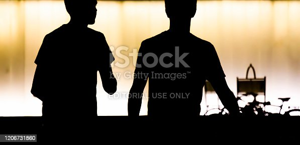 812812808 istock photo Silhouettes of two teen boys walking  in the summer night 1206731860