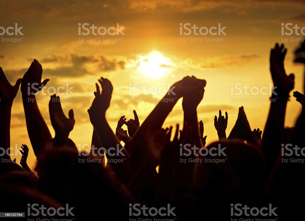 Silhouettes of upraised hands at music festival stock photo