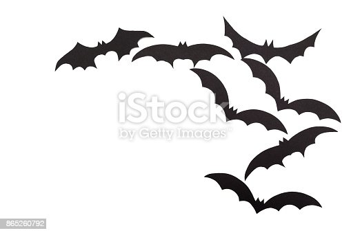 istock Silhouettes of volatile bats carved out of black paper are isolated on white 865260792