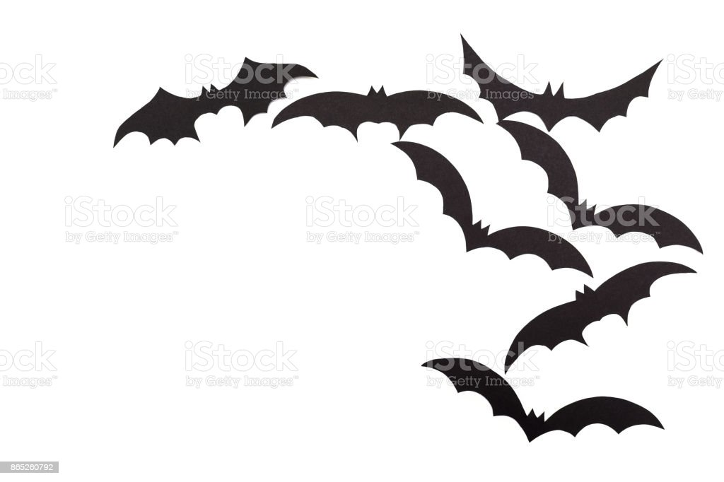 Silhouettes of volatile bats carved out of black paper are isolated on white stock photo