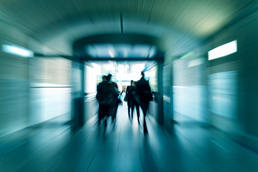 Silhouettes of walking people in subway corridor