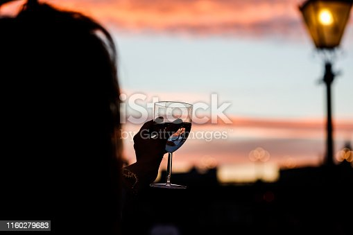 Silhouettes of woman drink glasses of champagne wine at sunset dramatic sky