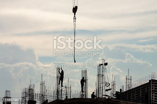 Moscow, Russia - May 12, 2018: Silhouette workers and crane - construction machinery on the roof construction site building on overcast background. Construction of a multi-storey building