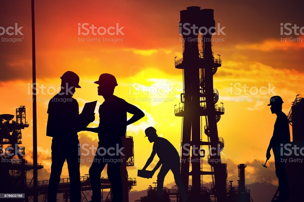 Silhouettes of workers working on construction site at suset. stock photo