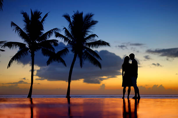 silhouettes of young couple at scenic sunset - pool schritte stock-fotos und bilder