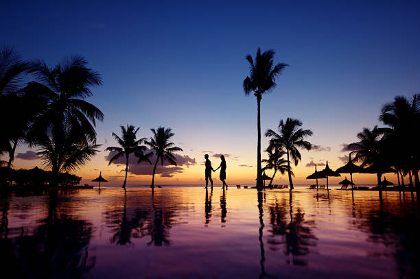 Silhouettes of young couple at scenic sunset Silhouettes of young couple at scenic sunset on tropical beach honeymoon stock pictures, royalty-free photos & images