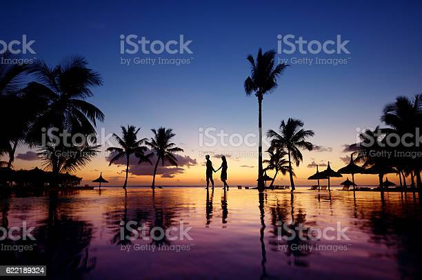 Photo of Silhouettes of young couple at scenic sunset