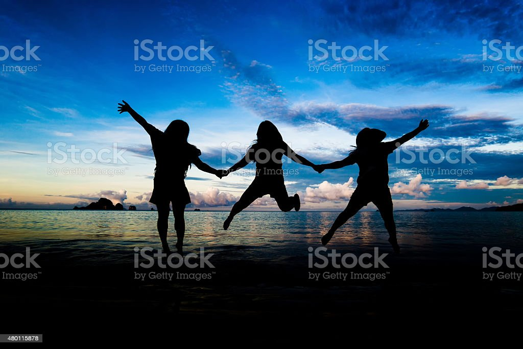 Silhouettes of young group of people jumping stock photo