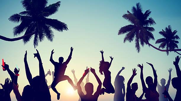 Silhouette di giovani festeggia su una spiaggia - foto stock