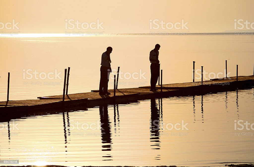 silhouettes on a pier royalty-free stock photo