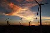 Silhouettes power generator wind turbine with sunset.