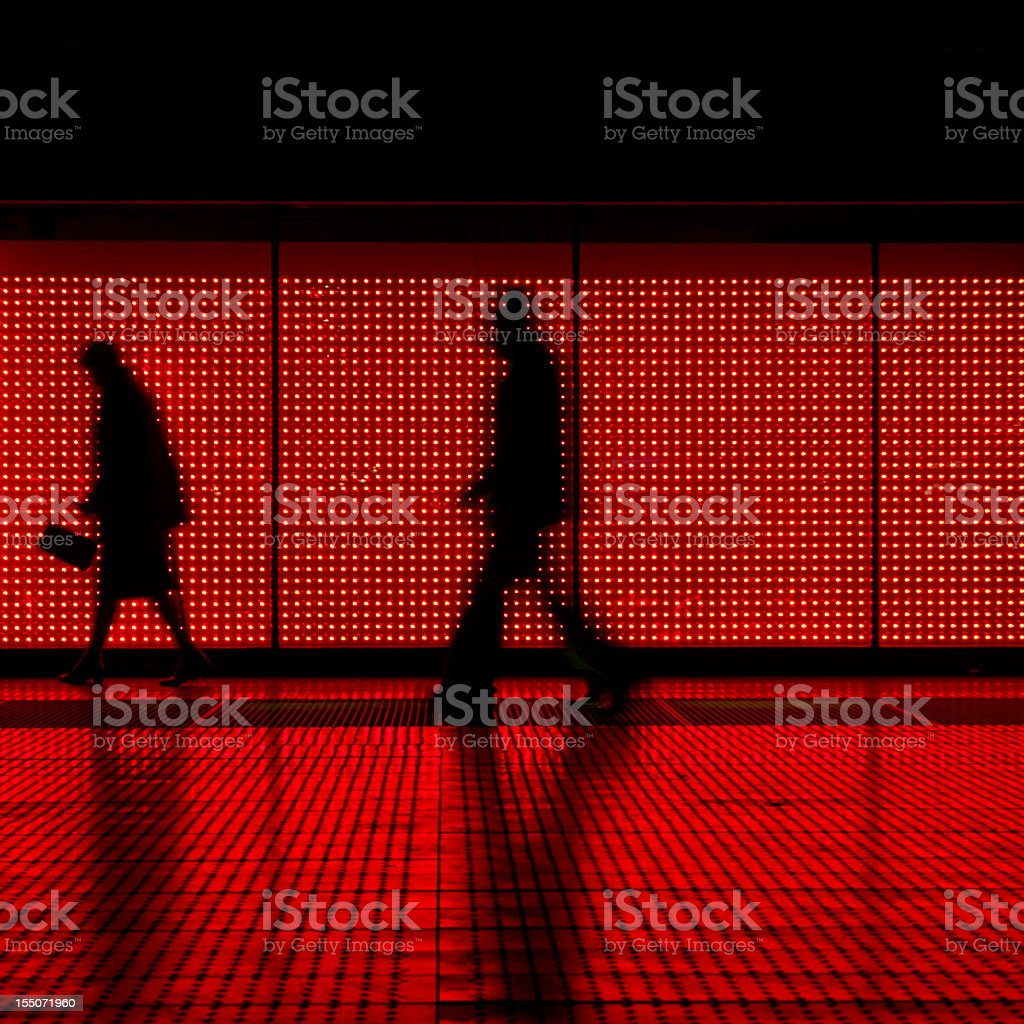 Silhouettes walking on a Moving sidewalk in red & black royalty-free stock photo