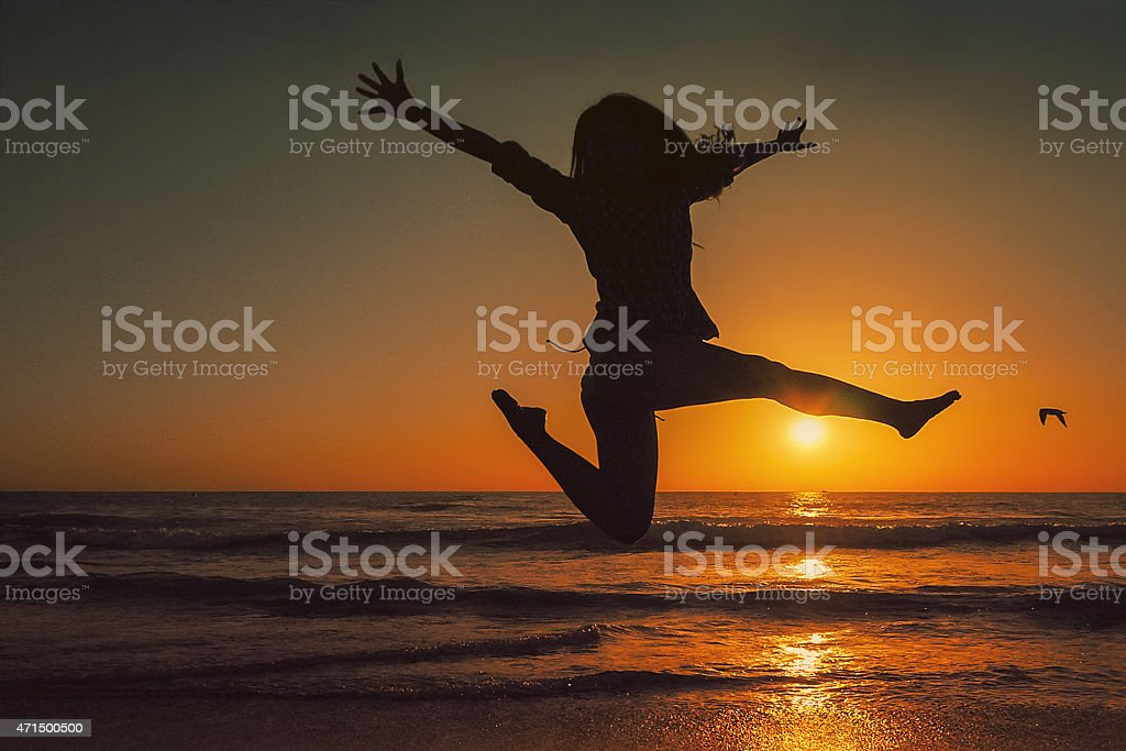 Silhoutte of woman jumping on beach at sunset stock photo