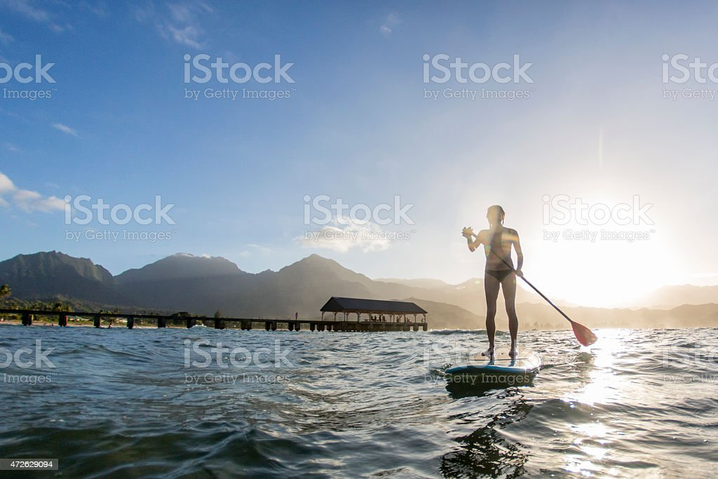 Silhoutte of Woman Paddle Boarding stock photo