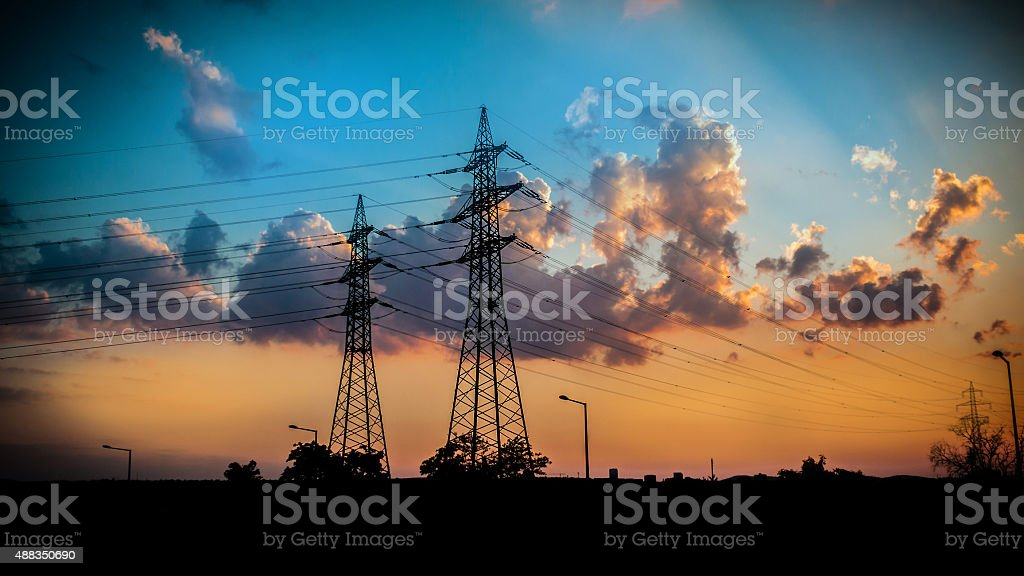 silhuettes of electricity pylons in the evening stock photo