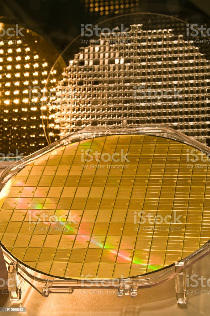 Silicon (in front), glass, and gold covered glass wafer (back) stock photo