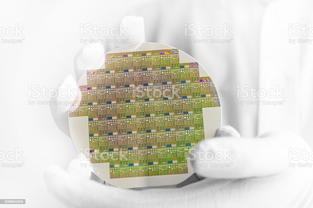 Silicon wafer in engineer's hands - clean room laboratory stock photo