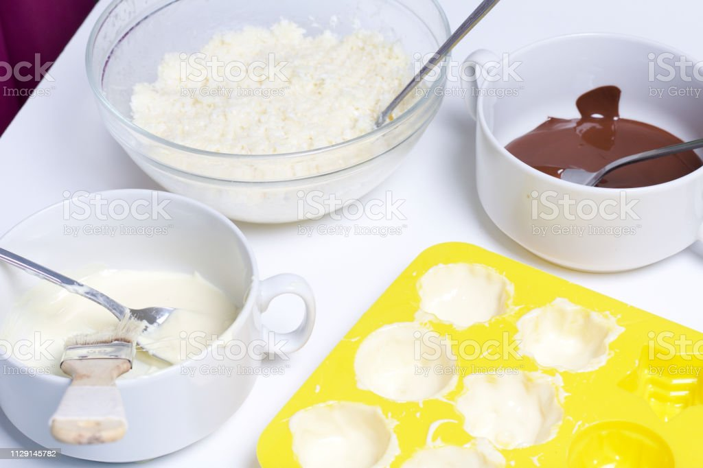 Silicone mold smeared with melted white chocolate. Ingredients for...