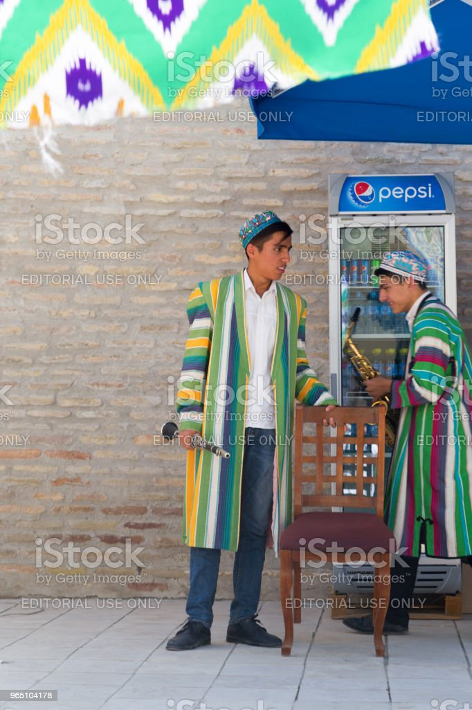 BUKHARA, UZBEKISTAN - MAY 25, 2018: Silk and Spices Festival 2018. Bukharian musicians in local dress dance, in Bukhara, Uzbekistan. royalty-free stock photo