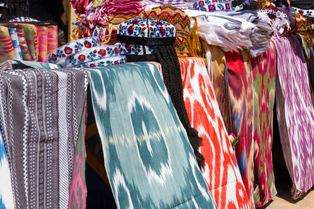 BUKHARA, UZBEKISTAN - MAY 25, 2018: Silk and Spices Festival 2018. Traditional Uzbek asian silk fabric shop in Bukhara, Uzbekistan. BUKHARA, UZBEKISTAN - MAY 25, 2018: Silk and Spices Festival 2018. Traditional Uzbek asian silk fabric shop in Bukhara, Uzbekistan muziekfestival stock pictures, royalty-free photos & images
