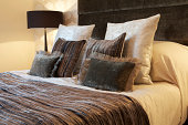 a group of silk cushions arranged on a bed in front of a velvet headboard. The rest of the bedding is also in silk. The warm colours are largely due to the bedside lamps and ceiling lighting. Looking for more images of cushions Then please click on the Lightbox link below...A>A