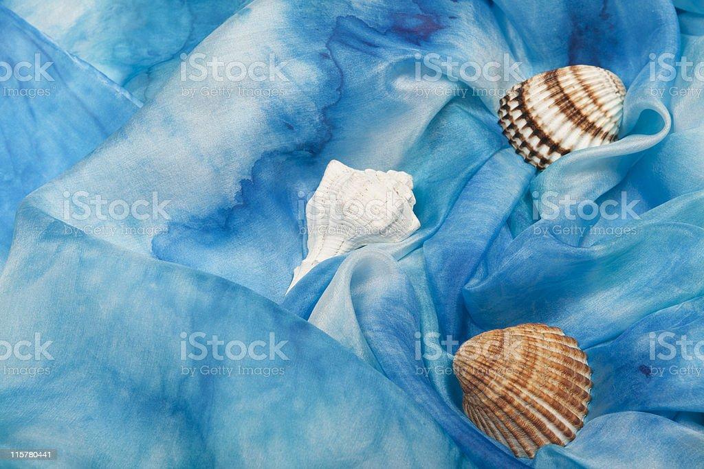 Silk fabric in sea blue color with seashells. stock photo