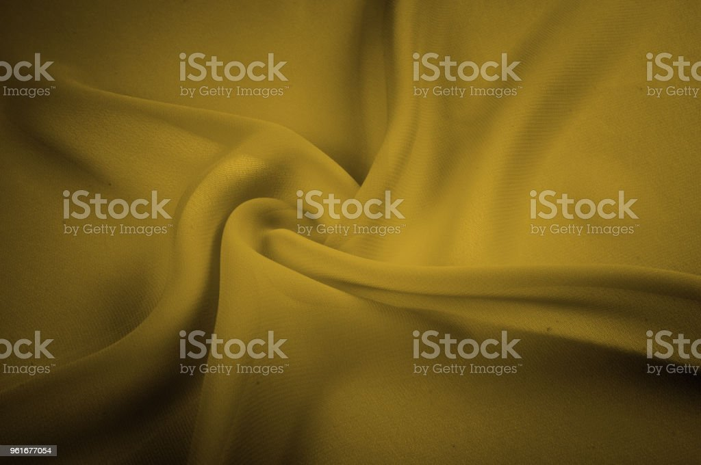 silk fabric is transparent, mustard, yellow. Chandeliers, light and abundant - all the characteristics of this fantastic fabric that you do not want to miss! Here we have a glamorous, light mustard stock photo