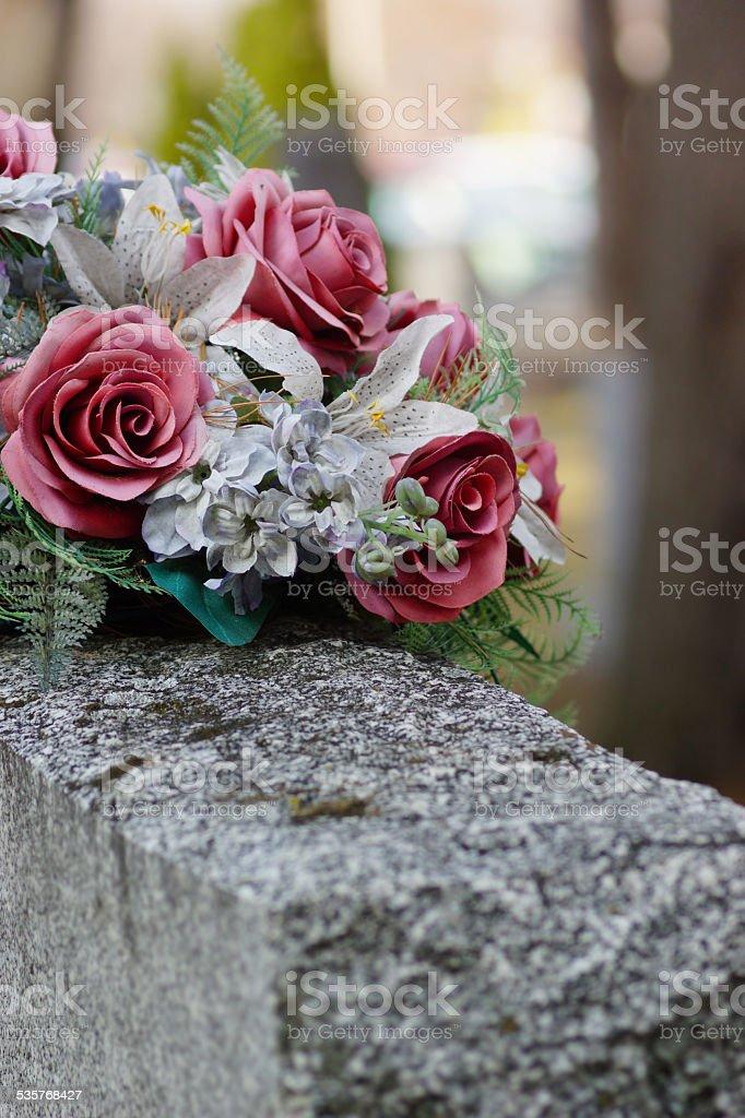 Silk flowers on a gravestone, soft focus stock photo