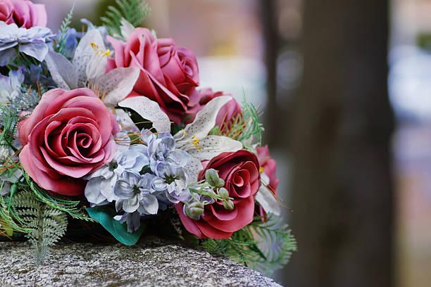 silk flowers on a gravestone, soft focus - graf stockfoto's en -beelden