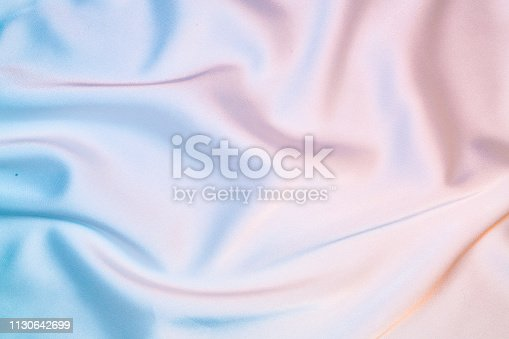Silk shiny fabric texture in pastel iridescent holographic colors