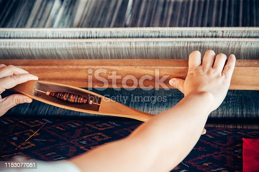 Silk weaving or Knitting silk cotton on the manual wood loom for homemade silk or textile production in thailand .