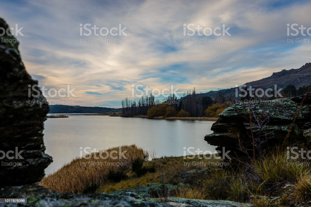 Silky smooth central Otago lake viewed from between two boulders with a cloudy sky stock photo