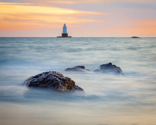 Silky Water Rocky Sunset Seascape with Lighthouse stock photo