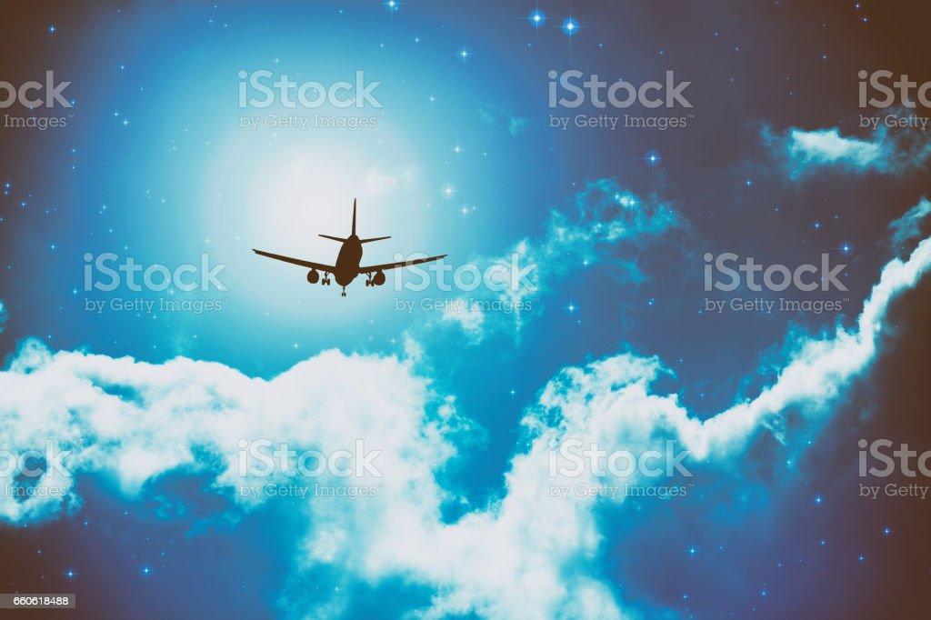 Sillhouette de un avión que volaba en una noche estrellada con algunas nubes. - foto de stock