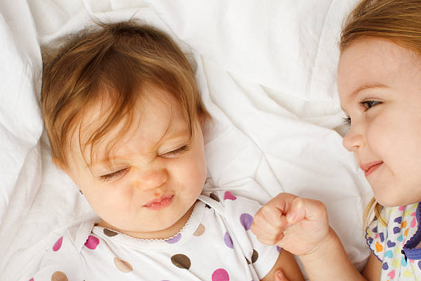 Silly baby in sheets with big sister stock photo