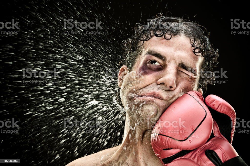 silly boxer man takes a punch in the face isolated on black.funny concept portrait stock photo
