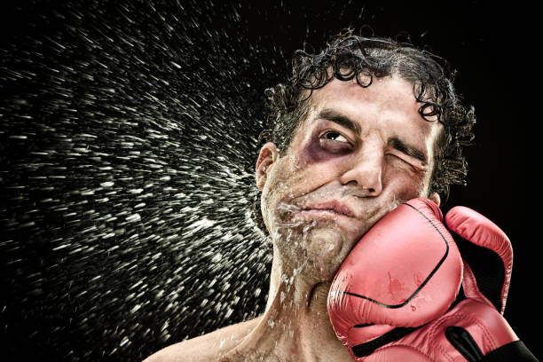 silly boxer man takes a punch in the face isolated on black.funny concept portrait - punching stock photos and pictures