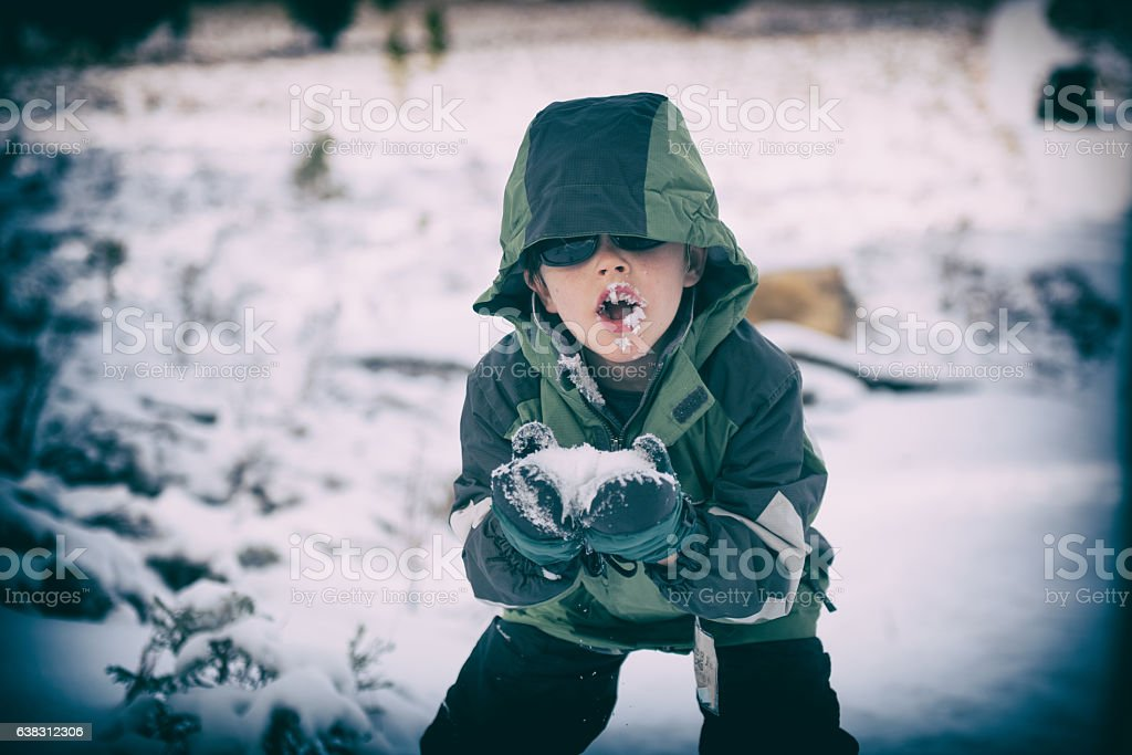 Silly boy eating snow stock photo
